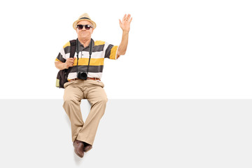 Mature tourist waving with his hand