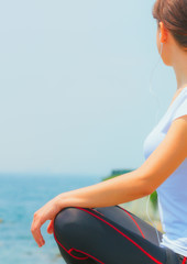 Girl sitting at seaside and relaxing, woman fitness