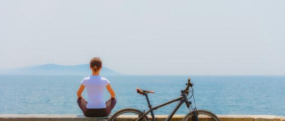 Cycling - Biker girl sitting at seaside, woman fitness