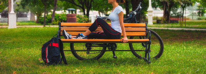 Biker girl relaxing in the park, woman fitness