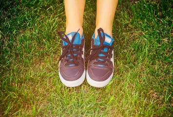 Girl sitting shoes closeup, green grass, woman fitness