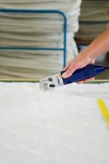 hand schneidet matratzenstoff