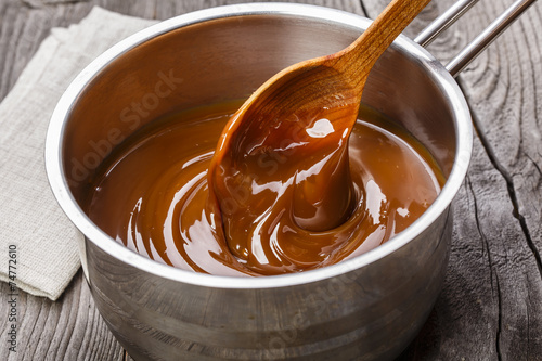 liquid caramel is poured into a gravy boat - 74772610