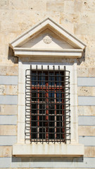 Stylish window with bars at old Ottoman fortress in Kos, Greece