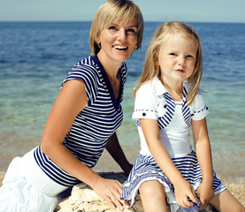 mother with daughter at sea cost together, happy family