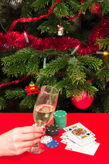 Hand holding a glass, red table, cards, Christmas deco