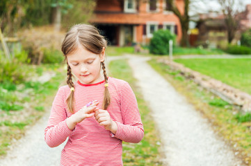 Adorable little girl playing alone outdoors in early spring