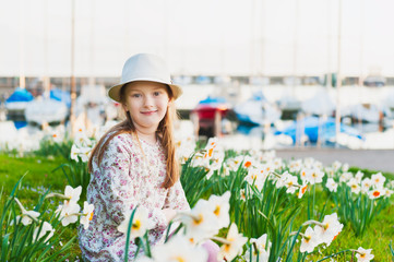 Spring portrait of adorable little girl by the lake