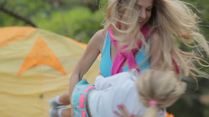 Energetic mom turns her daughter while relaxing on nature