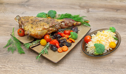 roasted leg of lamb with vegetables and herbs on a wooden backgr