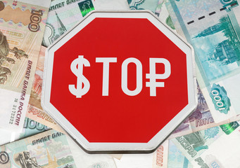 Finance concept with USD and Russian money as a stop road sign i