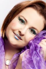 Glückliche Frau mit kräftigem Make Up schmiegt sich in ein Tuch