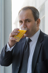 Handsome businessman drinking orange juice.