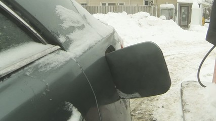 Pumping gasoline into a car on a cold day