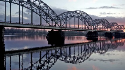 Train rides on fishnet bridge over the river at sunset