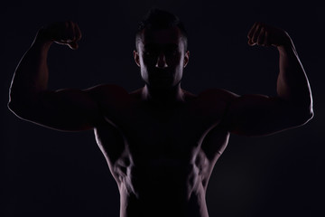 Silhouetted muscular man showing his biceps