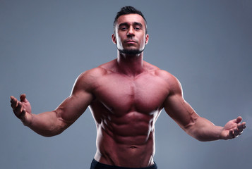 Portrait of a muscular man with nice abs over gray background
