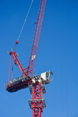 Red construction crane on clear blue sky