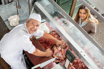 Butcher And Customer Smiling At Display Cabinet