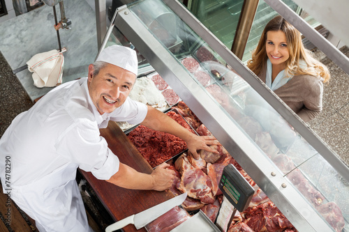 Butcher And Customer Smiling At Display Cabinet - 74782290