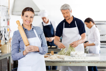 Happy Female Chef Holding Rolling Pin While Colleagues Preparing