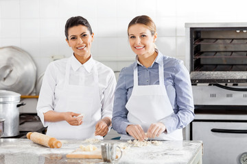 Happy Female Chefs Preparing Pasta At Counter