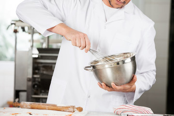 Midsection Of Chef Stirring Batter In Mixing Bowl At Kitchen