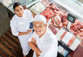 Happy Butchers Standing At Butchery Counter