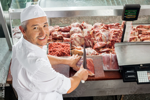 Butcher Cutting Meat At Display Cabinet - 74782649