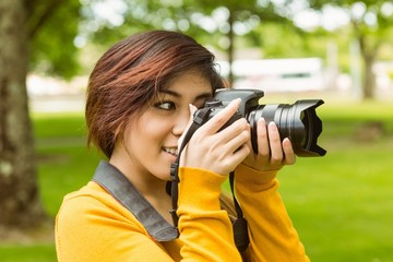 Beautiful female photographer at park