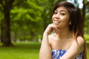 Beautiful woman with hand on chin in park