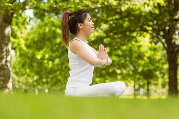 Healthy woman sitting with joined hands at park