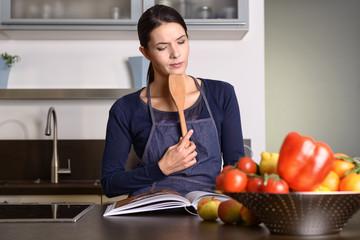 Ernste Frau in der Küche überlegt mit einem Kochbuch