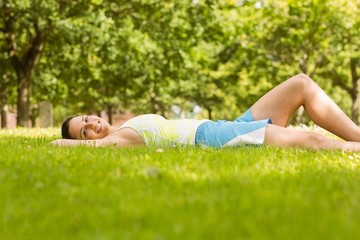 Happy fit brunette lying and relaxing on the grass