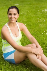 Happy fit brunette sitting on the grass