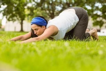 Calm brunette doing yoga on grass