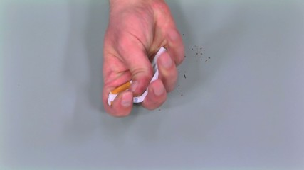 hands tearing many cigarettes