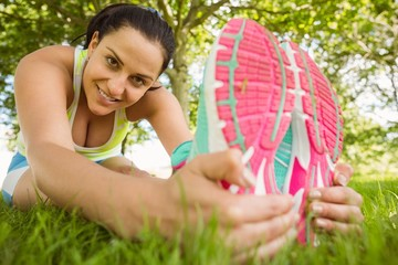 Smiling athletic brunette stretching on the grass