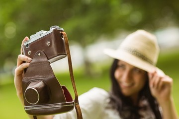 Smiling brunette taking a selfie with retro camera