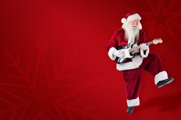 Composite image of santa claus has fun with a guitar