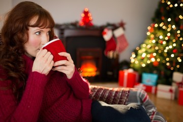 Pretty redhead drinking hot drink at christmas