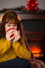 Beauty redhead drinking hot drink at christmas