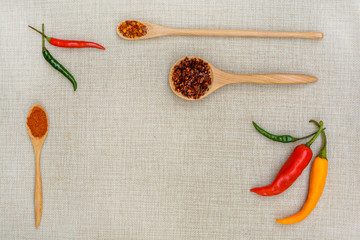 chili and paprika with wooden spoon on sackcloth