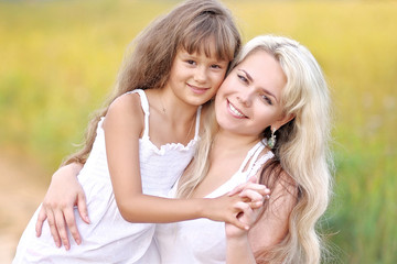Young mother hugging her daughter in summer nature