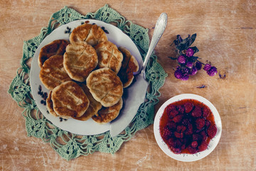 Pancakes with strawberry jam on a wooden background