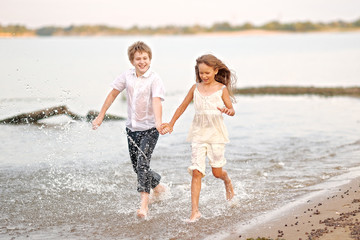 Portrait of a boy and a girl running on the beach