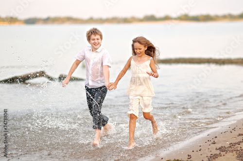 canvas print picture Portrait of a boy and a girl running on the beach