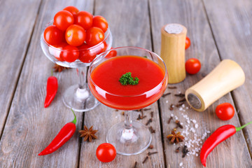 Tomato juice in goblet and fresh vegetables on wooden