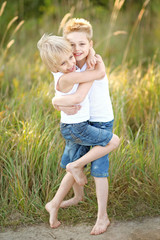 two children playing on meadow in summer