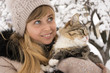 beautiful girl in mittens with a fluffy cat in winter